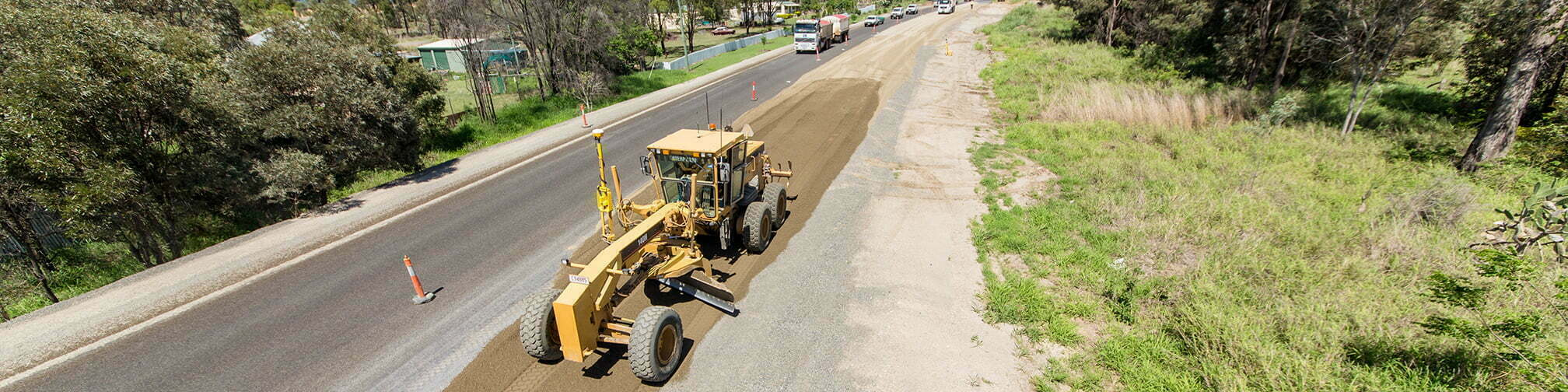 Image of a grader leveling the shoulder of a new road